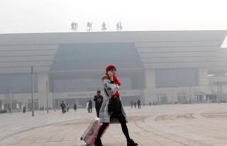 河南郑州东火车站外一名旅客在雾霾下带着口罩走过车站广场(中新社图片17/1/2017)
