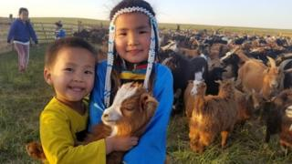 Technology Two Mongolian children with a goat