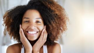 Una chica joven de raza mixta sonríe a la cámara