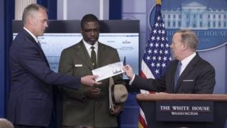 White House Press Secretary Sean Spicer (R) hands a check of funds being donated by US President Donald J. Trump (not pictured) to the National Park Service, to US Interior Secretary Ryan Zinke (L) and Tyrone Brandyburg (C).