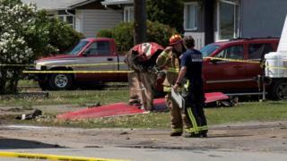 Fire officials talk in a residential neighbourhood street in front of the tail wreckage