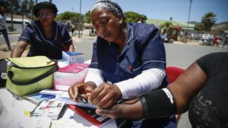 Nurses check the blood pressure of a woman.