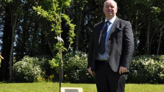 Chief Minister Howard Quayle standing next to a tree