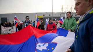 Manifestantes sostienen la bandera eslovena.