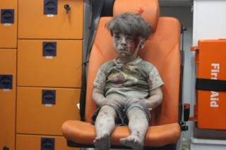 Photo showing Syrian boy Omran Daqneesh after his home was destroyed by an air strike in Qaterji, Aleppo, on 17 August 2016