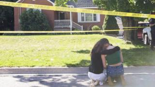 Two women console each other outside the house where the shooting took place