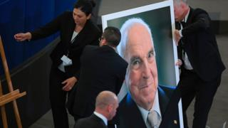 Officials install a portrait of Mr Kohl at the European Parliament