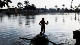 صياد يقف فوق قارب صيد وسط النهر