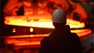 A worker watching steel melt