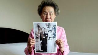 Lee Chun-ja, 88, holds up an old picture of her wedding in a hotel room (19 Aug 2018)