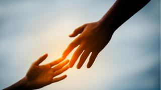 Dos manos uniéndose con simbología religiosa.