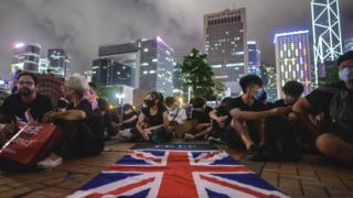 A British Union Jack flag is displayed as protesters gather along a fenced-off Victoria Harbour pier in Hong Kong