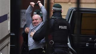 Paul McIntyre, the man charged with the murder of Lyra McKee, raises his arms as he arrives at Londonderry Magistrates' Court on 13 February 2020 in Londonderry, Northern Ireland