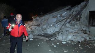 People walk past rubble as rescue operations begin in Villa Sant'Antonio village, near Visso, Marche region, Italy, on 26 October 2016