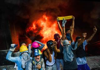 Anti-government demonstrators participate in an attack to the administration headquarters of the Supreme Court of Justice as part of protests against President Nicolas Maduro in Caracas, on June 12, 2017.