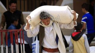 A man carries food aid from the UN's World Food Programme in Sanaa, Yemen (26 June 2018)