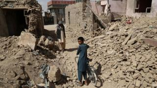 Afghan residents walk near destroyed houses after a Taliban attack in Ghazni on August 16, 2018.