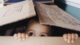 Ребенок выглядывает из картонной коробки