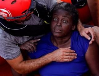 A crew member of NGO Proactiva Open Arms rescue boat embraces Josepha from Cameroon in central Mediterranean Sea
