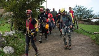 Members of Spanish rescue services escort four missing Portuguese men who were rescued after being trapped at a cave in Arredondo