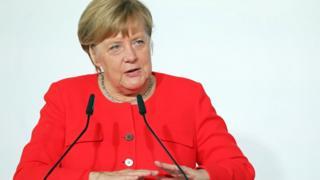 Almanya Başbakanı Angela Merkel oturarak konuşuyor