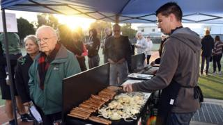 Sausages are cooked while people queue in the early morning light to vote in Australia