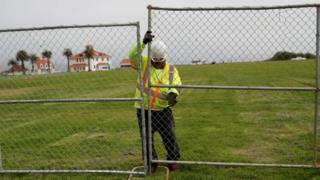 A worker installs a fence at Crissy Field in anticipation of Saturday's Patriot Prayer rally