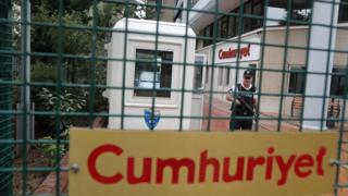 An armed private security officer on guard in front headquarter of Cumhuriyet daily newspaper in Istanbul, Turkey on 22 September