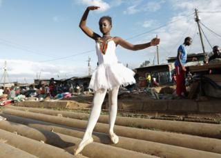 A young ballerina poses for a photo during a ballet street performance to showcase their skills in Kibera slum, Nairobi, Kenya - Saturday 30 November 2018