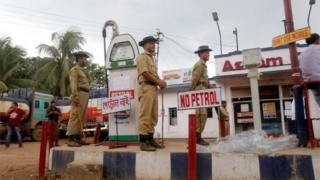 Policemen guard a fuel station during a protest against petrol crisis caused by damaged section of the Assam-Tripura national highway after incessant rains, in Agartala, India, July 29, 2016.