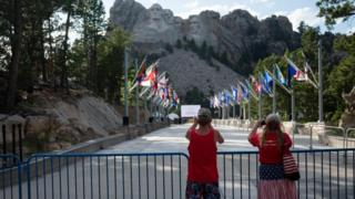 Visitors take pictures of Mount Rushmore National Monument in Keystone, South Dakota on July 2