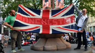 Two men hold union flag with Manchester emblazoned on it