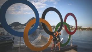 Members of the New Zealand rowing team take photos in front of the Olympic rings at the Rodrigo de Freitas Lagoon in Rio de Janeiro (01 August 2016)