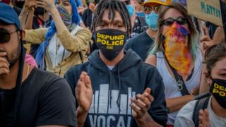 "Protestor wears mask saying ""defund the police"""