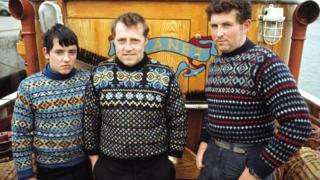 Three Fishermen pose wearing Fair Isle jumpers on the deck of their boat 'Planet' in the harbour of the Shetland Isle of Whalsay in June 1970