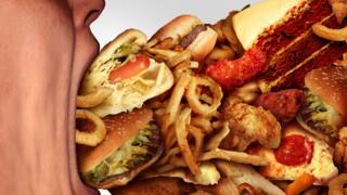 Persona comiendo mucha comida chatarra.