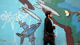 Man walks past mural on the wall of the former U.S. Embassy in Tehran, Iran, on May 9, 2018