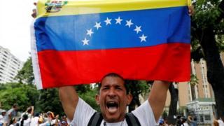 Hombre sostiene bandera de Venezuela.