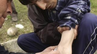 A Kyrgyz drug addict delivers a heroin injection to another drug addict in Osh, southern Kyrgyzstan (March 2005)