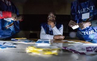 Independent National Electoral Commission (CENI) agents count votes during an electricity cut while watched by observers at Kiwele college in Lubumbashi on December 30, 2018