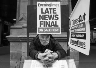 A vendor in the street outside Central Station, selling the Evening Times