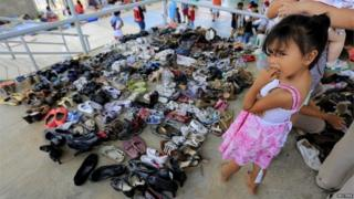 A Colombian girl who was deported looks on next to donated shoes in a temporary shelter