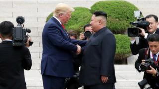 كيم جونغ اون ودونالد ترامب يتصافحان