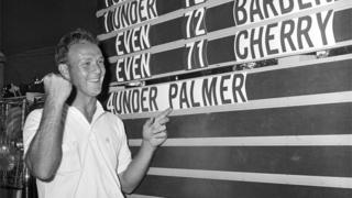 Arnold Palmer points to his name on the leader board at National Open golf tournament at the Cherry Hills Country Club in Denver, June 1960