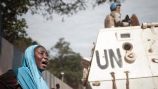 A woman reacts next to UN soldiers as inhabitants of the mainly Muslim PK5 neighbourhood demonstrate in front of the headquarters of MINUSCA, the UN peacekeeping mission in the Central Africa Republic, in Bangui, on April 11, 2018.