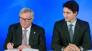 President of the European Commission Jean-Claude Juncker signs the Comprehensive Economic and Trade Agreement (CETA) as Canadian Prime Minister Justin Trudeau looks on at the European Council in Brussels on 30 October 2016.