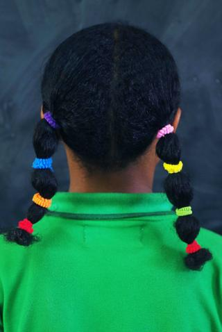 A girl wearing pigtails with several multi-coloured stands with her back to the camera