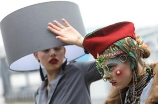 Participants pose for photographs as they take part in a Hat Walk