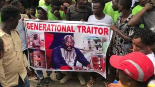Demonstrators hold a poster portraying Liberian President George Weah as they gather outside the Liberian Mansion in Monrovia on June 7, 2019 during an anti-government march to protest at inflation and corruption.