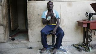 A volunteer vigilante sits outside his house after a fight against Boko Haram